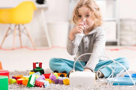 Niño pequeño que usa un inhalador en el suelo de su habitación, rodeado de juguetes