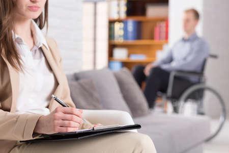 psique: Mujer haciendo notas con un hombre sentado en una silla de ruedas