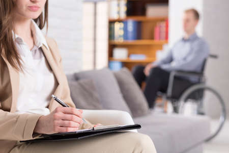 confide: Woman making notes with a man sitting on a wheelchair Stock Photo