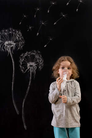 chalk drawing: Little boy having an inhalation in front of a blackboard with a dandelion and its seeds drawn on it