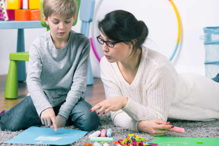 Boy and female pedagogue working with commitment on the carpet Stock Photo