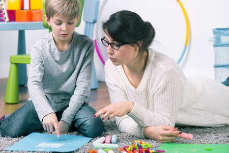 Boy y pedagogo sexo femenino que trabaja con el compromiso en la alfombra Foto de archivo
