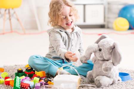 asthmatic: Little child playing with his mascot elephant as if he was blowing its nose, next to an inhalator Stock Photo