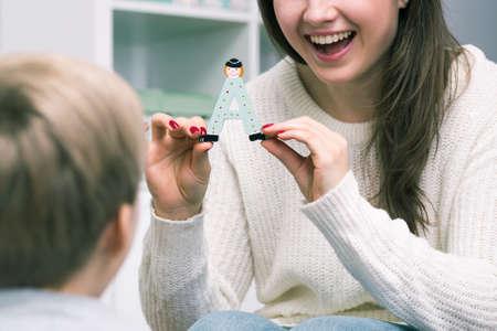 """pedagogista femminile sta mostrando alla sua pupilla una lettera """"A"""""""