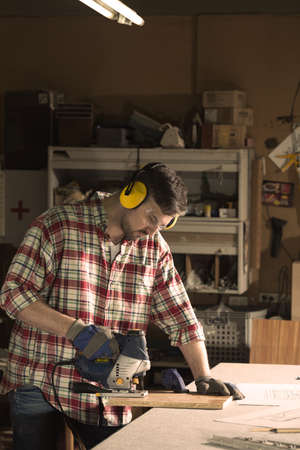 protective goggles: Focused man in protective goggles and headphones is cutting wood Stock Photo