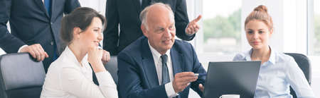 panoramic business: Shot of an old businessman having a meeting with his coworkers Stock Photo