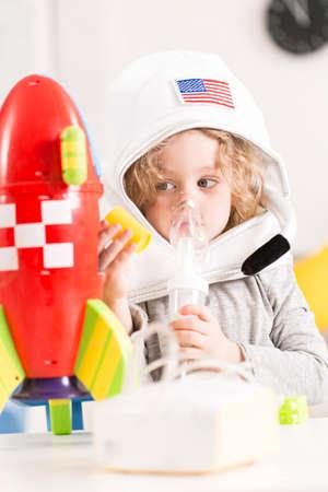 Little boy pretending to be an astronaut white having an inhalation