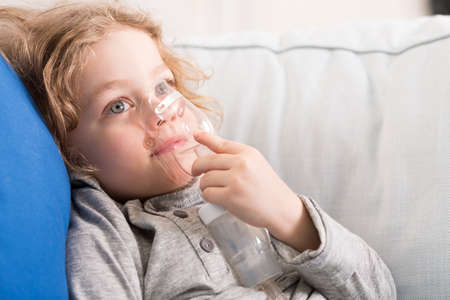 inhalator: Close-up of a little blonde boy holding an inhalator and breathing air from it Stock Photo