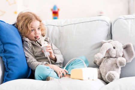 inhalator: Little boy with worried face sitting among soft cushions on a sofa, breathing with an inhalator Stock Photo