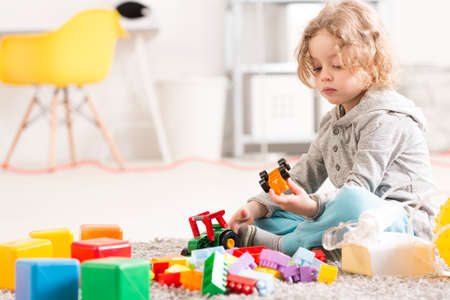 Little boy playing with toy cars beside an inhalator standing on the floor