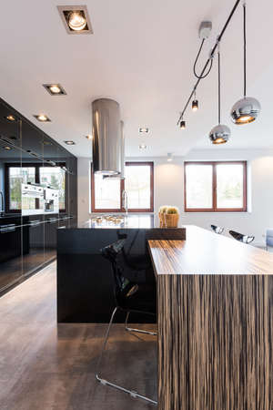 ascetic: Cavernous interior of a modern kitchen and dining room with large countertop and suspended metal lights