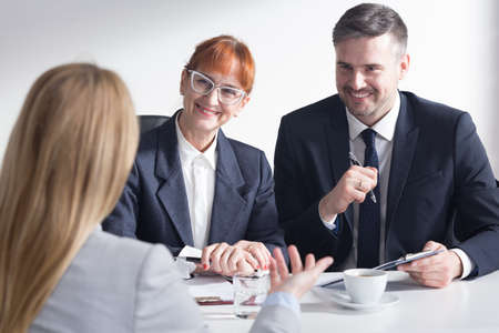 recruiters: Recruiters are listening with satisfaction the presentation of female job applicant Stock Photo