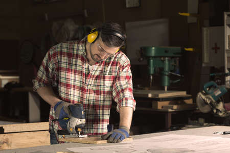 protective goggles: Focused carpenter in protective goggles and headphones is working in his workshop Stock Photo