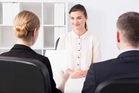 recruiters: Young woman and recruiters during corporation job interview Stock Photo