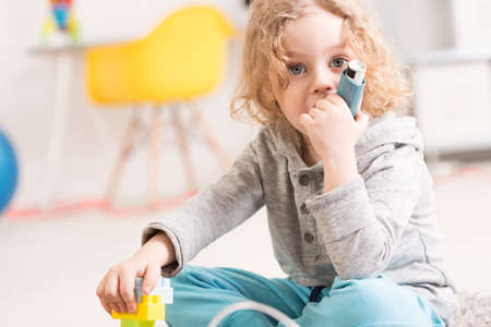 inhale: Close-up of a little boy holding a small inhalator while playing with building blocks