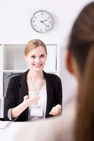 gesturing: Young businesswoman gesturing during talk with female colleague