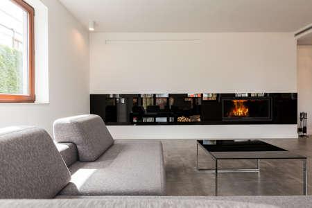 Muy moderna y espaciosa sala de estar dispuestos en estilo minimalista, con una chimenea en una de las paredes