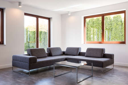 living room sofa: Corner of a very modern living room with a large grey sofa and a glass coffee table standing by two windows Stock Photo