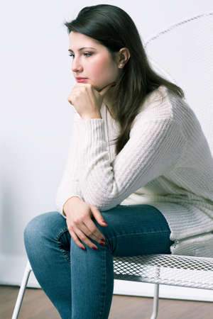 chagrin: Sad and worried mother is sitting and waiting for her child in waiting room Stock Photo