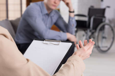 confide: Therapy session with elegant man and wheelchair on the floor behind him Stock Photo