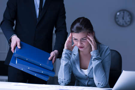 burnout: Young overworked and burnout woman sitting at desk