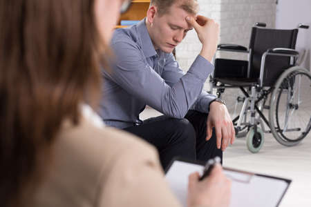 confide: Depressed man in thereapy center with the wheelchair at the background Stock Photo