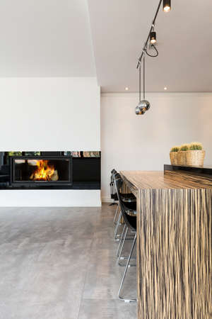 tall chimney: Very modern living room in minimalist style, with fireplace and an eating bar with bar chairs