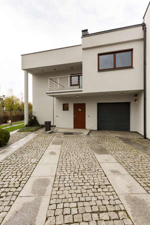 Outside of a modern detached house seen from the cobbled driveway