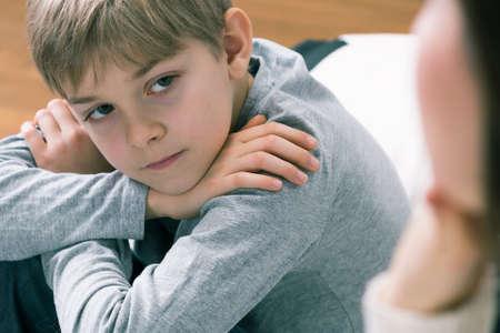 El muchacho joven está escuchando y mirando a alguien