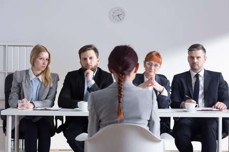 recruiters: Female job applicant sitting in front of the Selection Committee. Recruiters listening intently to her speech
