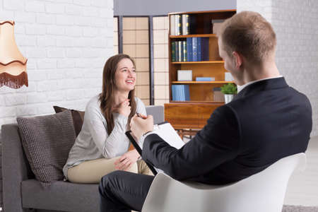 confide: Smiled woman talking with her man psychologist in therapy center
