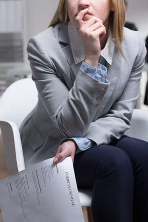 company job: Female job applicant holding her C.V. and wondering about something