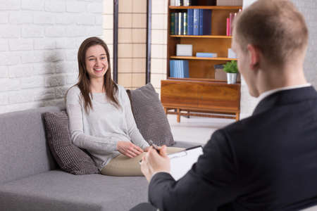 confide: Smiled woman sitting near her man psychologist during the therapy session