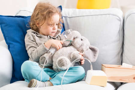 asthmatic: Picture showing a little boy on a sofa, pretending to be inhaling his mascot elephant Stock Photo