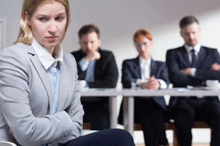 recruiters: Female job applicant sitting worried on a chair and recruiters are dissatisfied Stock Photo