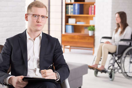 confide: Young woman on a wheelchair behind the elegant man psychologist Stock Photo