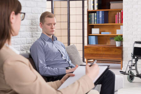confide: Elegant young man sitting in therapy room and stearing at one point