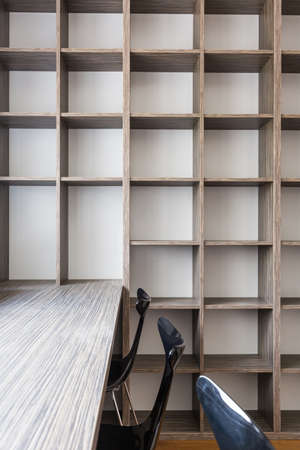 rack arrangement: Empty office room in a house, with large desk and fitted bookshelf Stock Photo