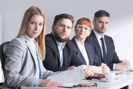 recruiters: Recruiters are sitting behind the desk. One of them are holding a application papers