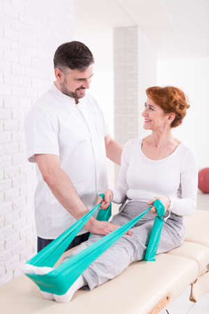 professional woman: Shot of a woman using an exercise band for a rehabilitation and her physiotherapist watching over her Stock Photo