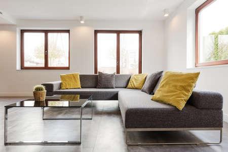 非常に近代的で光の家のインテリアの大きなコーナー ソファとガラス コーヒー テーブル 写真素材