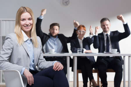 glee: Female job applicant is gently smiling and recruiters are rising hands with glee and satisfaction