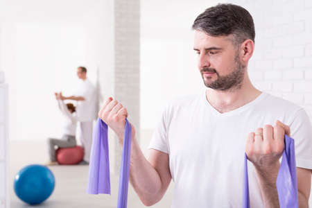 middleaged: Shot of a middle-aged man using an exercise band at the gym