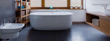Shot of a grey bathroom with a big white bath