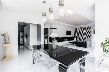 Luxurious black and white dining room with black table and ghost chairs, open living room in the background Archivio Fotografico