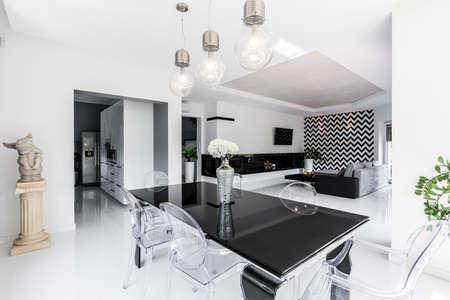 Luxe zwarte en witte eetkamer met zwarte tafel en ghost stoelen, open woonkamer op de achtergrond Stockfoto