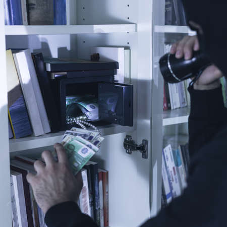 safe money: Close-up of a burglar robbing a home safe of money and jewellery Stock Photo