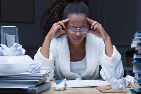 test deadline: Female student with headache learning for exam at night Stock Photo