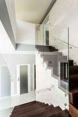chromed: White staircase with wooden stairs, glass balustrade and chromed railing Stock Photo