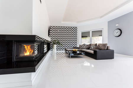 Bright and spacious luxurious living room with fireplace, large sofa, small table and pattern wallpaper Stok Fotoğraf